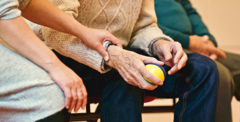 Sanitaria coge del brazo a un mayor que tiene una pelota