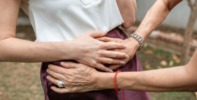 Una mujer mayor toca la tripa de una embarazada