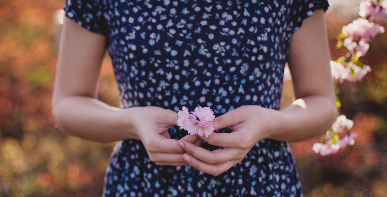 Una mujer sujeta una flor con la mano