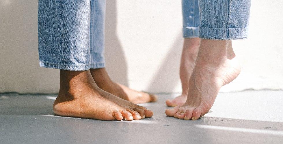 Los pies de una pareja mientras ella se levanta