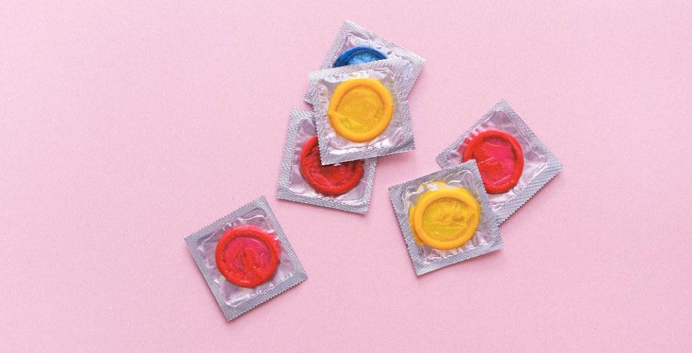 Preservativos de colores con un fondo rosa