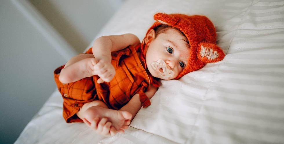 Un bebé recién nacido con chupete y vestido de rojo