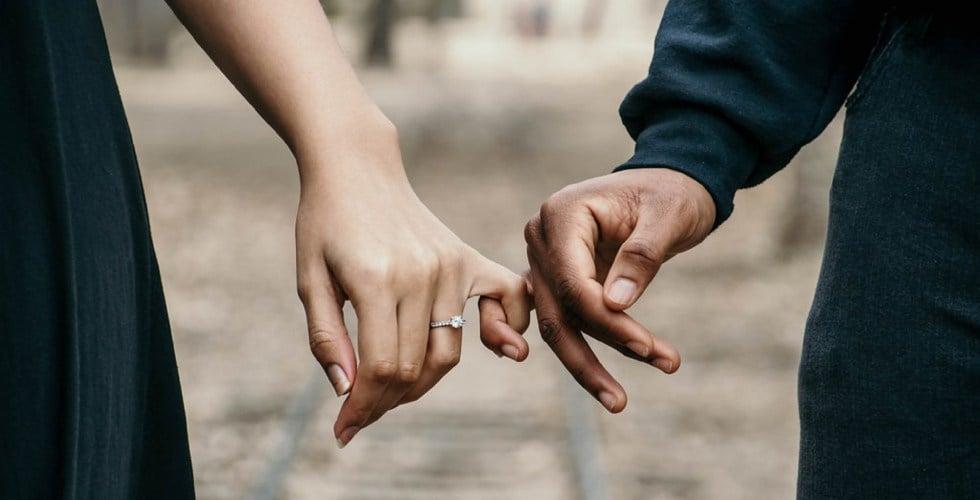 Una pareja se agarra del dedo meñique