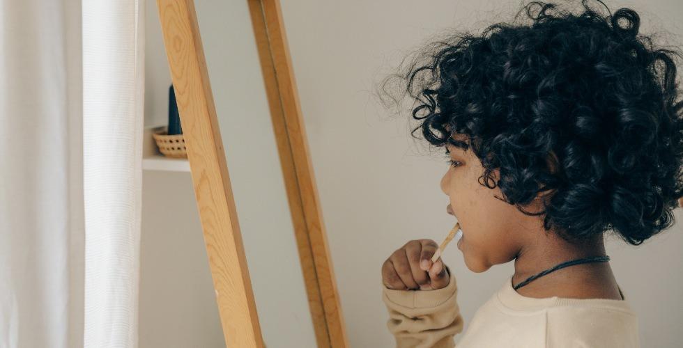 Un niño se lava los dientes frente al espejo