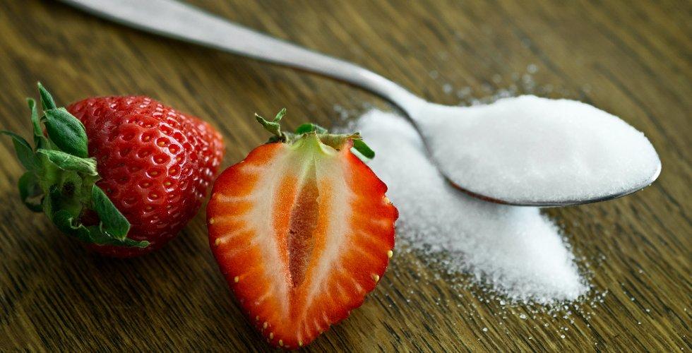 Una cuchara con azúcar y unas fresas partidas