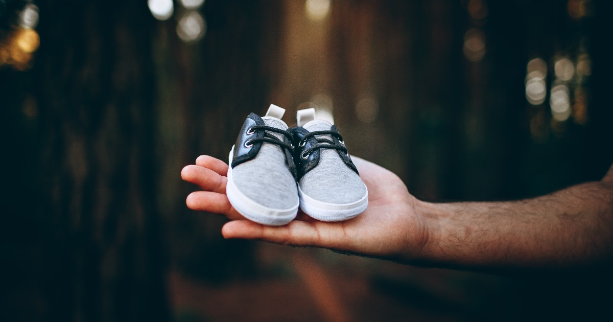 Un padre sujeta unos zapatos de un bebé