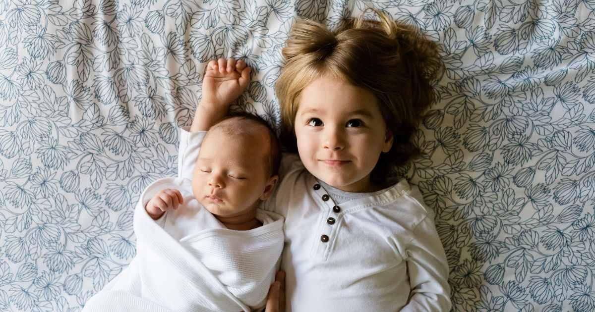 Dos niños sobre la cama de sus padres